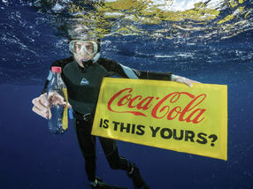 """A Greenpeace diver holds a banner reading """"Coca-Cola is this yours?"""" and a Coke bottle found adrift in the Great Pacific Garbage Patch. Even hundreds of kilometres from any inhabited land, plastic can be found polluting our environment."""